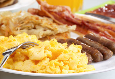Scrambled eggs with bacon and sausage on a plate